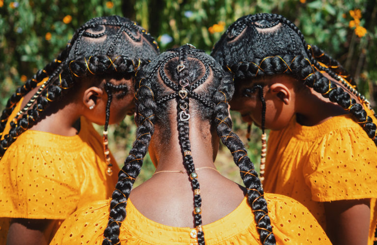 Three young women with elaborately braided hair