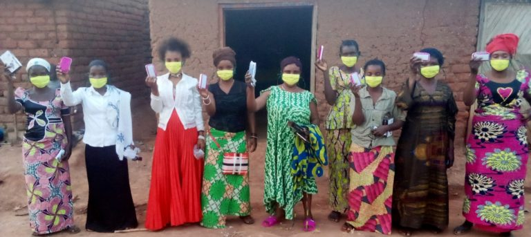 A group of women wearing face masks hold up cards
