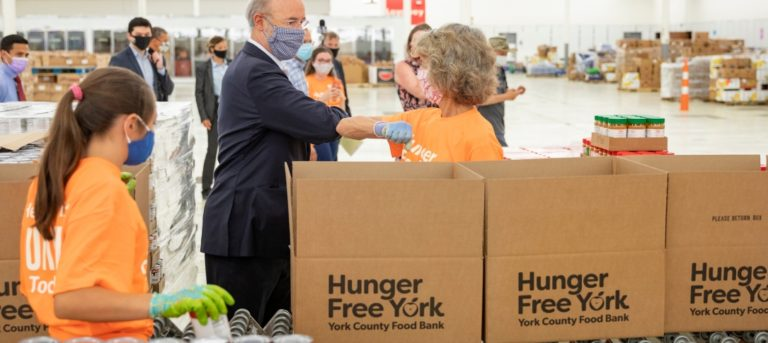 People wearing masks and orange t-shirts work at tables with boxes of food